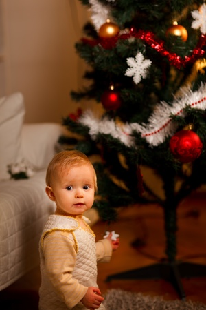 baby near christmas tree: Portrait of adorable baby near Christmas tree  Stock Photo