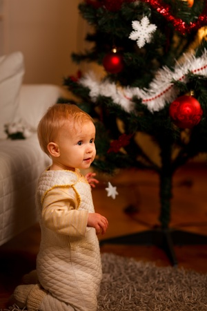 baby near christmas tree: Lovely baby near Christmas tree looking on side  Stock Photo