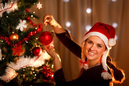 Beautiful woman hanging toy on Christmas tree  photo