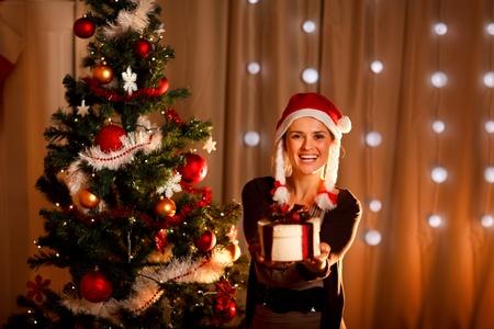 Beautiful girl near Christmas tree presenting gift box  photo