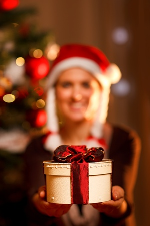 Closeup on hand presenting gift box and smiling woman and Christmas tree in background