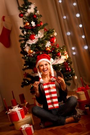 Beautiful woman near Christmas tree opening gifts Stock Photo - 11383517