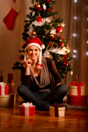 Beautiful female in Santa Hat near Christmas tree and present boxes  photo