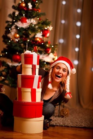 Pretty woman near Christmas tree looking out from pile of present boxes Stock Photo - 11374642