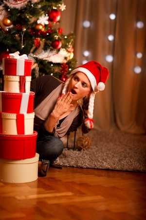 Beautiful girl near Christmas tree surprised looking on tower of present boxes 