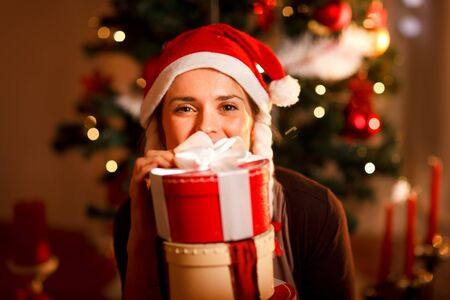 Portrait of female near Christmas tree hiding behind pile of present boxes   Stock Photo