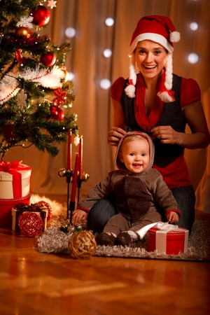 Happy mother and adorable baby in suit of Santas little helper  photo