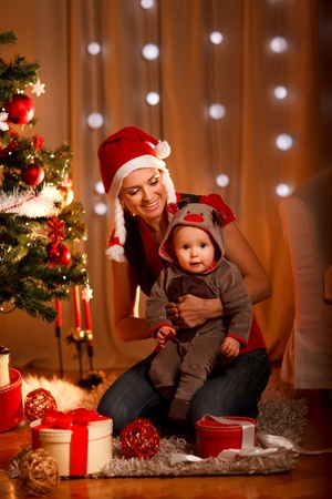 baby near christmas tree: Smiling mother with lovely baby sitting near Christmas tree  Stock Photo