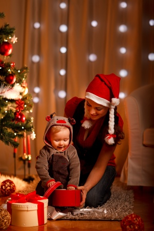 Young mother with happy baby opening present box near Christmas tree  photo