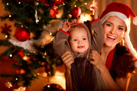 xmas baby: Portrait of happy mother and adorable baby in suit of Santas little helper  Stock Photo