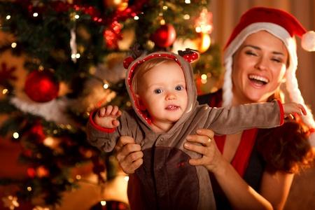 Happy mother playing with baby near  Christmas tree Zdjęcie Seryjne