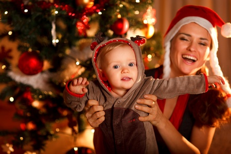 Happy mother playing with baby near  Christmas tree