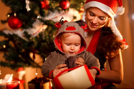 Young mother helping interested baby open present box at Christmas tree  photo