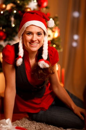 Smiling female sitting near Christmas tree   photo