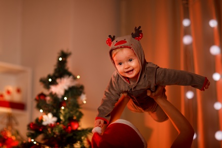 Adorable baby having fun near Christmas tree   photo