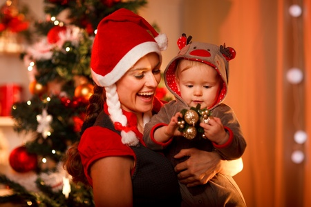 baby christmas: Smiling mother playing with lovely baby near Christmas tree  Stock Photo
