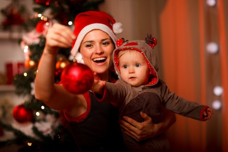 baby near christmas tree: Happy mother showing Christmas ball  to baby near Christmas tree  Stock Photo
