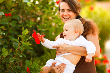 interrogatively: Happy mother showing flower to her baby on street