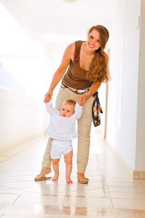 Smiling mother helping baby to walk