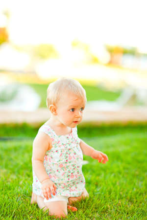 interrogatively: Interested baby playing on grass