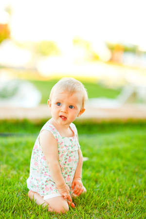 interrogatively: Thoughtful baby playing on grass  Stock Photo