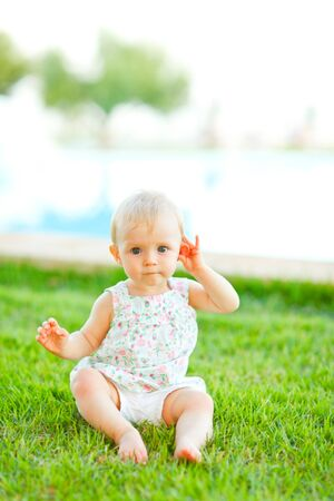 interrogatively: Portrait of adorable baby sitting on grass