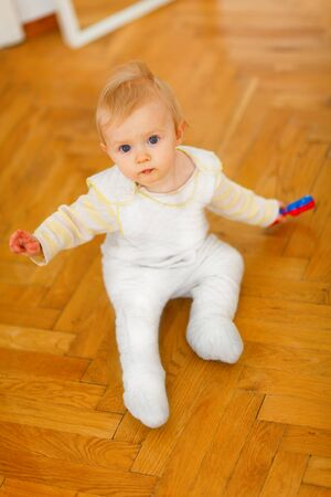 interrogatively: Lovely baby sitting on floor