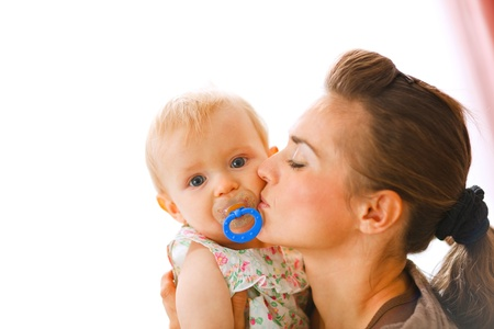Young mother kissing baby with soother