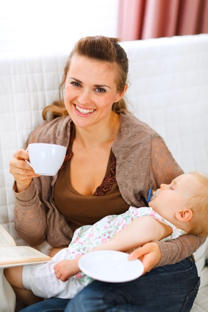 Happy mother resting while baby sleep by having tea and reading book