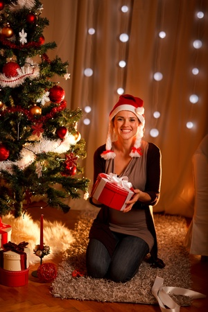 Portrait of pretty girl near Christmas tree holding gift photo