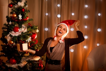 Happy girl in Santa hat near Christmas tree with present box  photo