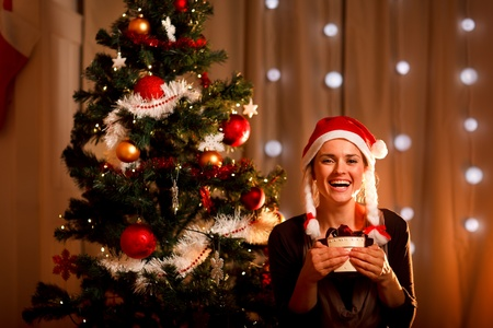 Portrait of smiling young woman near Christmas tree with present box  photo
