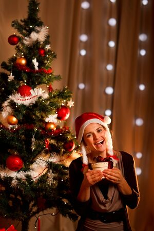 Portrait of happy girl near Christmas tree with present box  photo