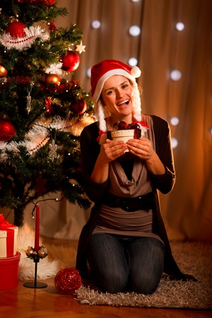 Happy young woman near Christmas tree hugging present box  photo