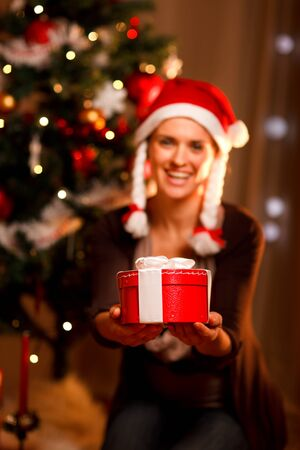 Smiling woman near Christmas tree presenting gift box. Focus on gift  photo