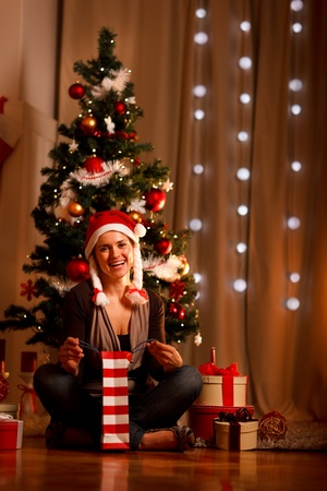 Smiling young woman near Christmas tree opening Christmas present  photo