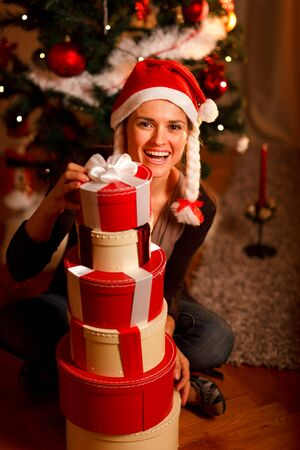 Smiling young woman near Christmas tree looking out from pile of present boxes   photo