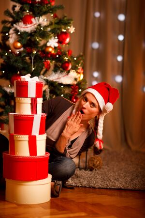 Surprised beautiful woman near Christmas tree looking on tower of present boxes   photo