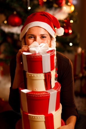 Woman near Christmas tree hiding behind pile of present boxes  Stock Photo - 11640603