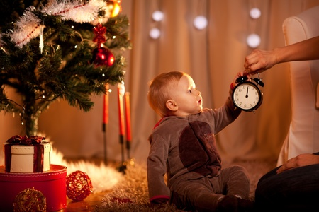 Lovely baby near Christmas tree holding with mother alarm clock  photo