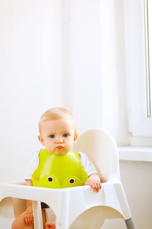 babero: Retrato de la hermosa bebé comer untado sentado en la silla de bebé
