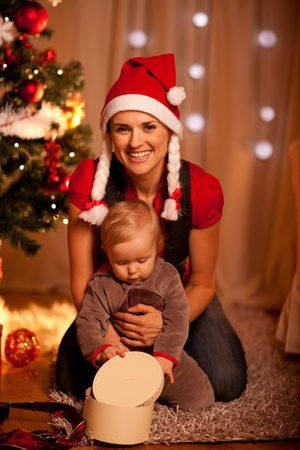 baby near christmas tree: Adorable baby near Christmas tree opening Christmas gifts with mother