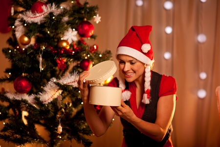 Happy young woman near Christmas tree looking inside present box  photo