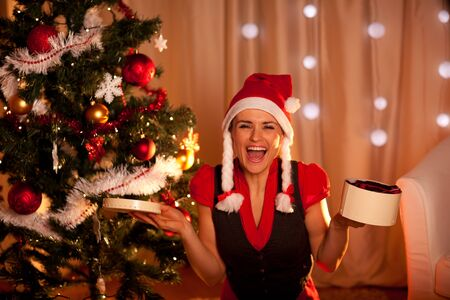 Happy young woman near Christmas with open gift  photo