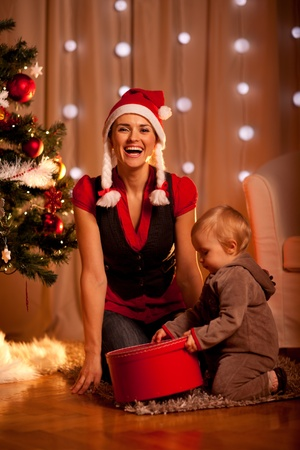 baby near christmas tree: Happy young mother with lovely baby opening present box near Christmas tree