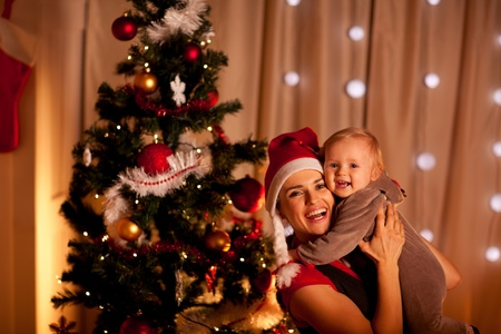 baby near christmas tree: Portrait of smiling young mother with beautiful baby  near Christmas tree