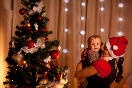 baby near christmas tree: Portrait of adorable baby on mamas hand near Christmas tree