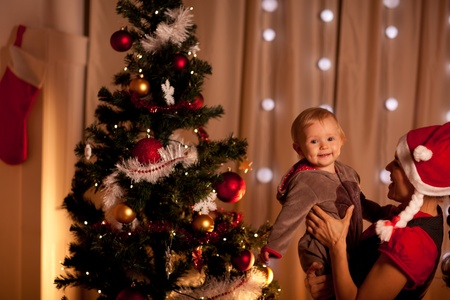 baby near christmas tree: Portrait of lovely baby on mamas hand near Christmas tree