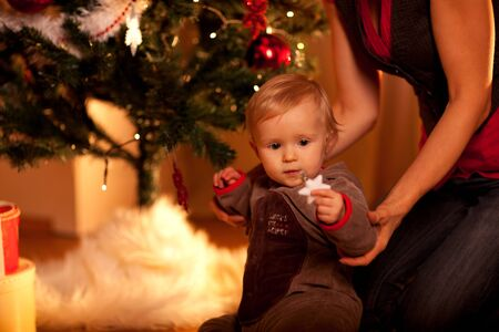 baby near christmas tree: Lovely baby sitting with mama near Christmas tree and looking on Christmas toy  Stock Photo