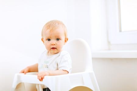smeared baby: Hermoso beb� sentado en silla de beb� Foto de archivo